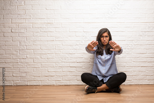 Fototapety, obrazy: Young indian woman sit against a brick wall serious and determined, putting hand in front, stop gesture, deny concept