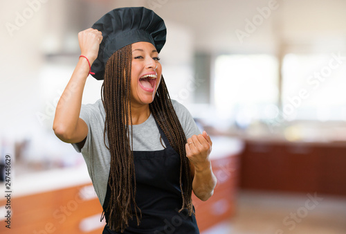 Fotografía  Portrait of a young black baker woman very happy and excited, raising arms, cele