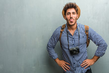 Young Handsome Traveler Man Wearing A Straw Hat, A Backpack And A Photo Camera Expression Of Confidence And Emotion, Fun And Friendly, Showing Tongue As A Sign Of Play Or Fun