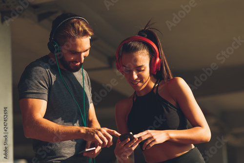 Young sports couple making break and listening to music and laughing - 247452694