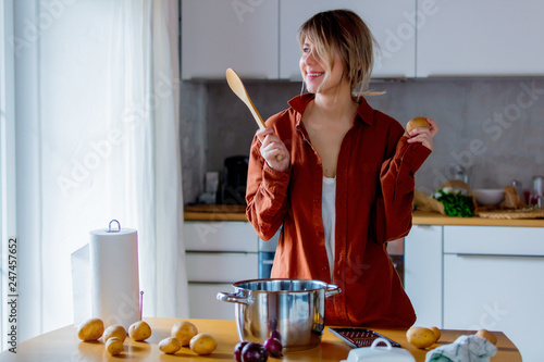 Beautiful housewife with pot cooking on kitchen.