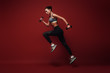 Long jump. Sportswoman jumping over red background with dumbbells in her hands
