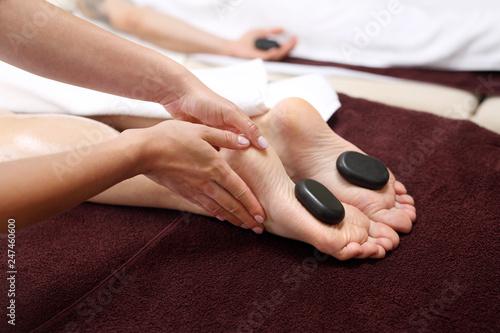 Obraz Masaż gorącymi kamieniami.  Kobiece stopy z kamieniami bazaltowymi, relaks w salonie spa. - fototapety do salonu