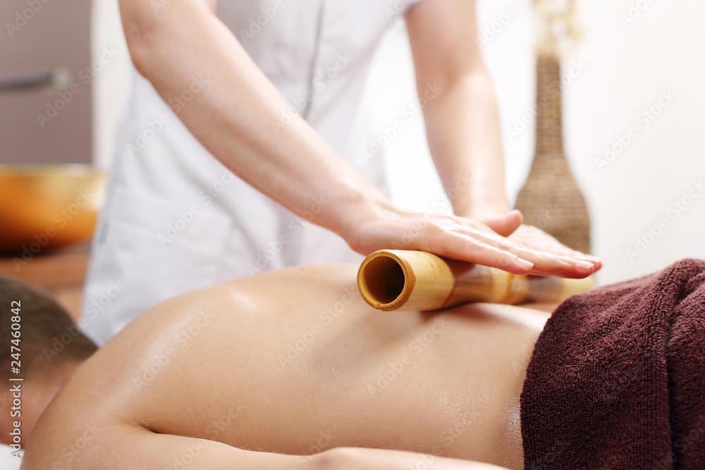 Fototapeta Masaż bambusowy. Relaksacyjny masaż bambusem. Masażysta masuje ciało przy użyciu bambusowych kijów.