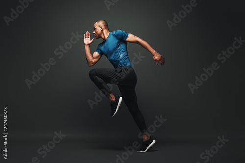 Deserve Victory. Sportsman jumping over dark background, he is ready to run
