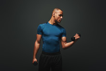 Achieving Best Results. Dark Skinned Sportsman Working Out With Dumbbells Over Dark Background