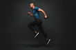 canvas print picture - Everything you've ever wanted is on the other side of fear. Dark skinned sportsman jumping over dark background. He is ready to run