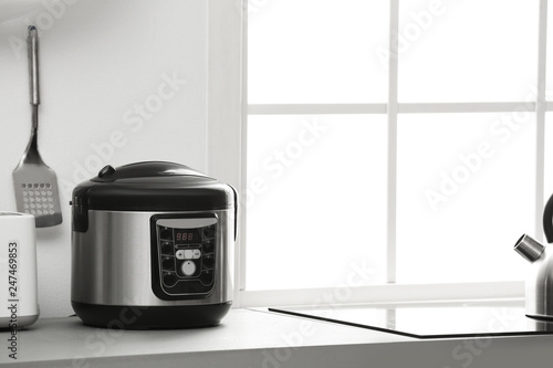 Modern electric multi cooker on kitchen countertop. Space for text