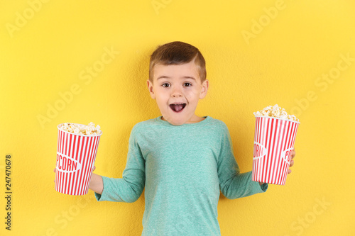 Cute little boy with popcorn on color background