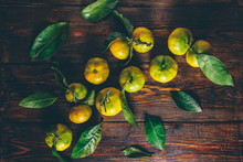 Yellow-green Tangerines With Leaves Over Wooden Surface