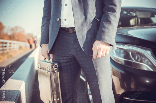 Cuadros en Lienzo a businessman standing near in front of luxury car holding brief case or diplom
