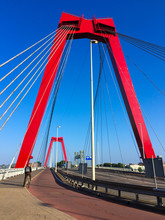 Cyclist Crossing The Willemsbrug Bridge Spanning The Nieuwe Maas River In Rotterdam, The Netherlands. Red Bridge Pylons And Cables Against Blue Sky