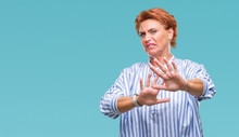 Atrractive Senior Caucasian Redhead Woman Over Isolated Background Disgusted Expression, Displeased And Fearful Doing Disgust Face Because Aversion Reaction. With Hands Raised. Annoying Concept.