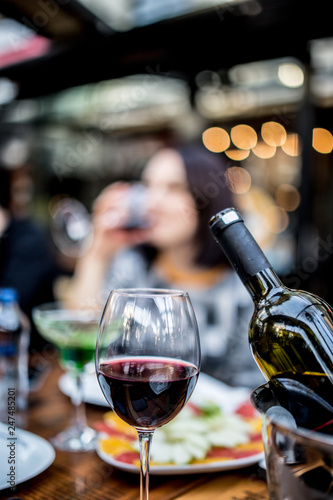 red wine glass and bottle with ice bucket infront of blurred wine drinking girl