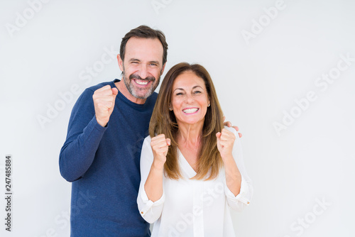 Fotografia  Beautiful middle age couple in love over isolated background excited for success with arms raised celebrating victory smiling