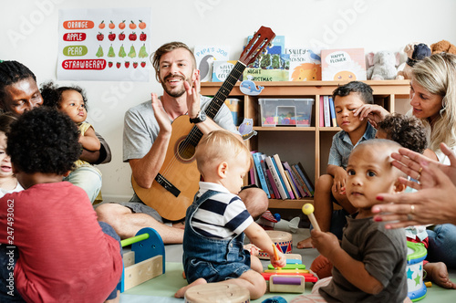 Nursery children playing with musical instruments in the classroom - 247493062