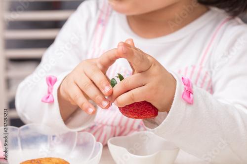 Fotografia  幼児の女の子いちごを持っていじいじしている