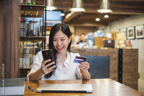 b9f07b70d04 Young beautiful asian woman using smart phone and credit card for shopping  online in coffee shop