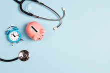 Piggy Bank With Stethoscope And Alarm Clock On Blue Background. Top View With Copy Space.