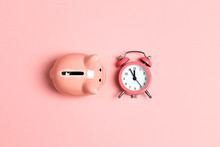 Piggy Bank And Classic Alarm Clock On Pink Background. Time To Saving, Money, Banking Concept.  Flat Design, Top Down Composition.