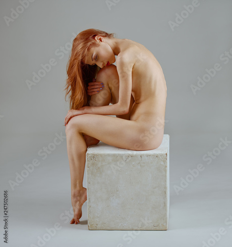 elegant slim elegant long-haired girl posing completely nude sitting on a cube in the studio on a white seamless background