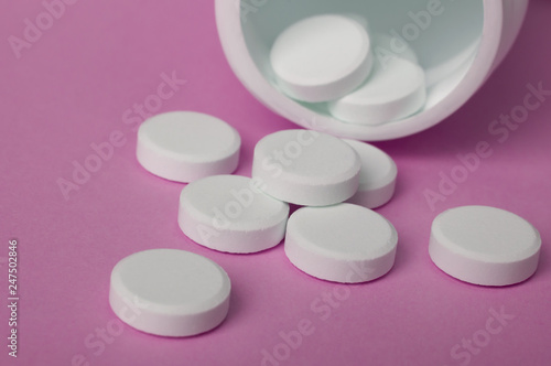 Fotografia  white round pills pouring out of the medicine bottle on pink background, closed up and selective focus