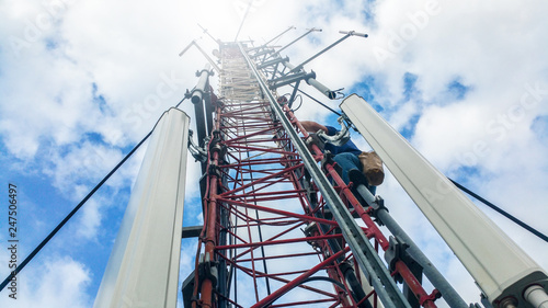 Worker climbing on a very high metal construction radio cellular network antenna Fototapete