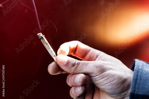 Young man passing marijuana joint.