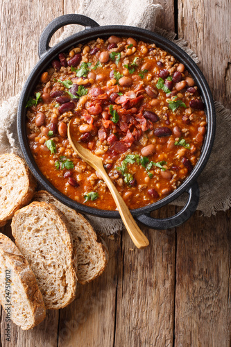 Delicious cowboy stew of beans with ground beef, bacon in a spicy sauce closeup in a bowl. Vertical top view