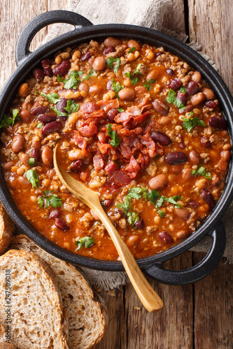 American cowboy beans with ground beef, bacon in a spicy sauce close-up. Vertical top view