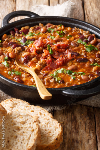 cowboy bean stew with ground beef, bacon in a spicy sauce close-up in a bowl. vertical