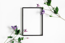 Flowers Composition. Purple Flowers, Photo Frame On Pastel Gray Background. Spring Concept. Flat Lay, Top View, Copy Space