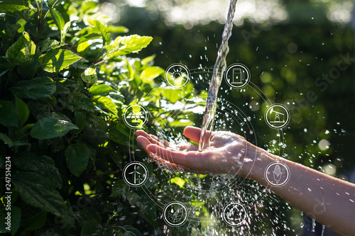 Fotografía  Water pouring in woman hand with icons energy sources for renewable, sustainable development