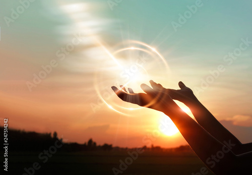 .Woman hands praying for blessing from god on sunset background Fotobehang