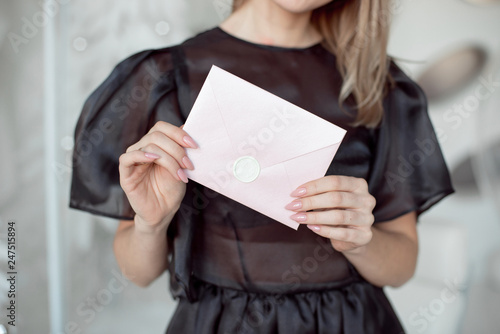 Fotografía  close-up photo of a female hands holding a pink invitation envelope with a wax s