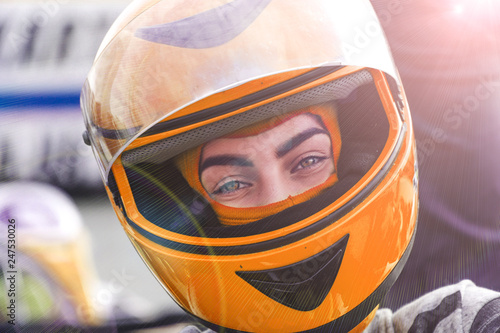 Recess Fitting F1 Orange helmet Close up on beautiful motorcycle woman driver taking off her red helmet