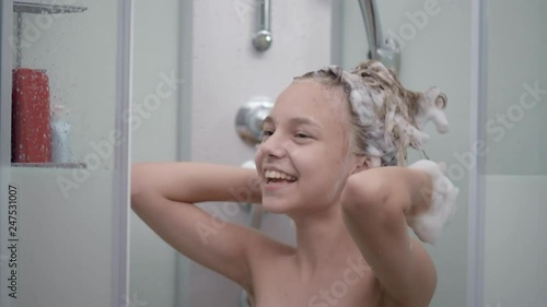 Vídeo de Smiling young girl bathing under a shower at home. Beautiful teen girl taking shower and washing in the bathroom. Happy child washing head, face and body with water. no Adobe Stock