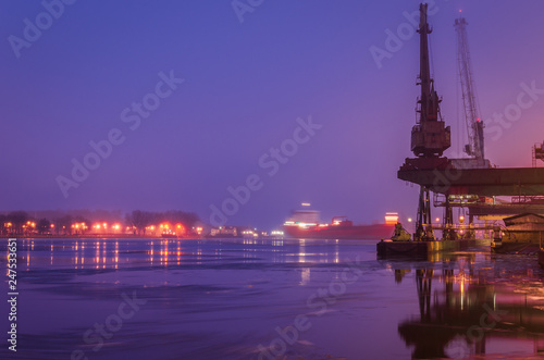 Fotobehang Poort SEAPORT AT DAWN - The cargo ship maneuvers to transhipment wharf in Swinoujscie