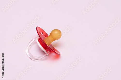 Fotografie, Tablou Baby new red pacifier on pink background.