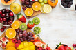 Leinwandbild Motiv Healthy raw fruits background, cut mango, strawberries raspberries oranges plums apples kiwis grapes blueberries cherries, on white table, copy space, top view, selective focus