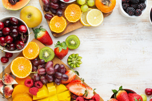 Healthy raw fruits background, cut mango, strawberries raspberries oranges plums apples kiwis grapes blueberries cherries, on white table, copy space, top view, selective focus