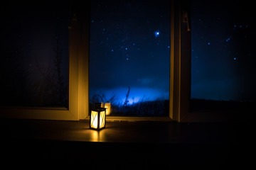 Night scene of stars seen through the window from dark room. Night sky inside dark room. Long exposure shot