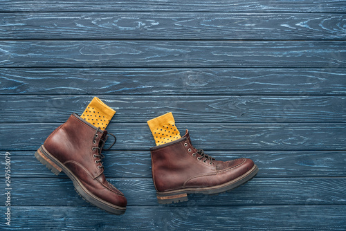 Top view of brown shoes and yellow socks on wooden background