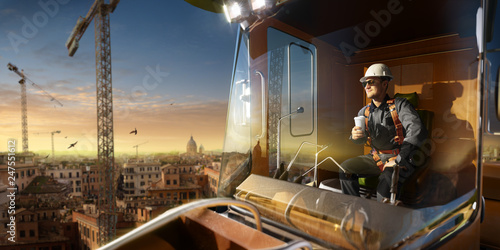 Happy engineer feel success after good work. He sit a top of crane cabin drink coffee and looking beautiful sunset