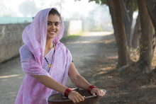 Smiling Rural Woman Or Daily Wage Labourer In Saree Carrying An Iron Gold Pan In Hand And A Tiffin Box To Work.