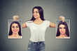 woman holding pictures with good and bad emotions having mood swings and smiling at positive herself
