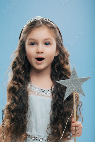 Foto  Small little child female princess wears crown and dress, holds magic wand, has long dark curly hair poses over blue background