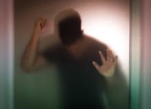 Sad Man Shadow Behind Translucent Glass.