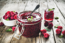 Homemade Raspberry Jam In Two Jars With Raspberries And Mint