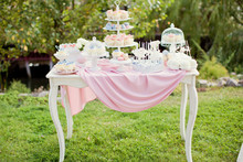 Candy Bar With Blue, Pink And White Cupcakes, Macaroons And Cake Pops